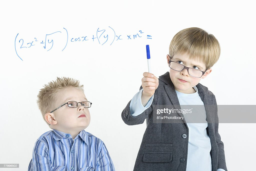 Two young boys working on a mathematical sum together : Stockfoto
