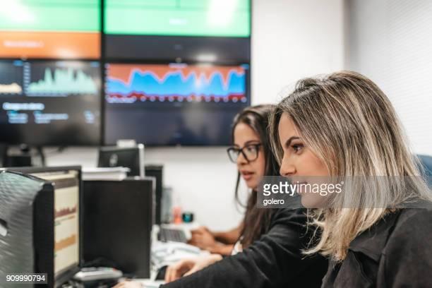 大きなオフィス内のコンピューターで働く 2 つの若いブラジルの女性