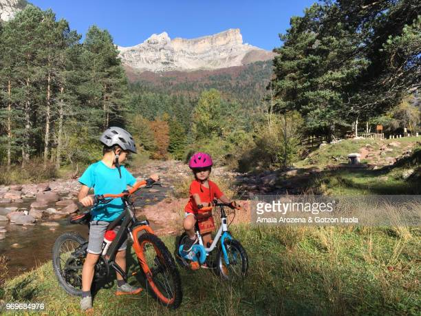 Two young brothers biking in Hecho Valley. Huesca province, Spain