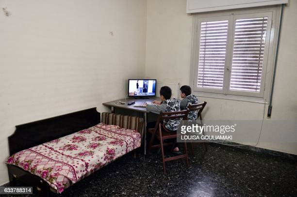 Two young brothers from Syria read their German language homework on January 31 2017 in an apartment in Athens rented by their family through a...