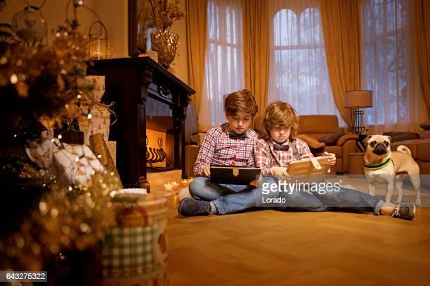 屋内設定でお祝いデコレーションのクリスマス シーンの 2 人の若い兄弟
