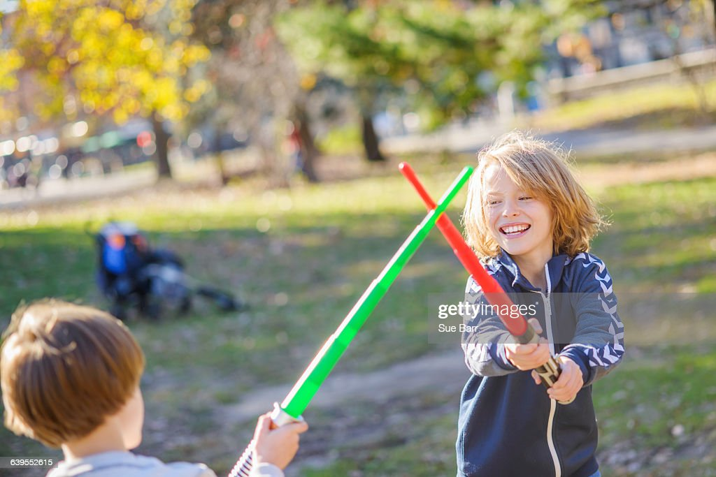 Two young brothers, play fighting with laser swords : Stock Photo