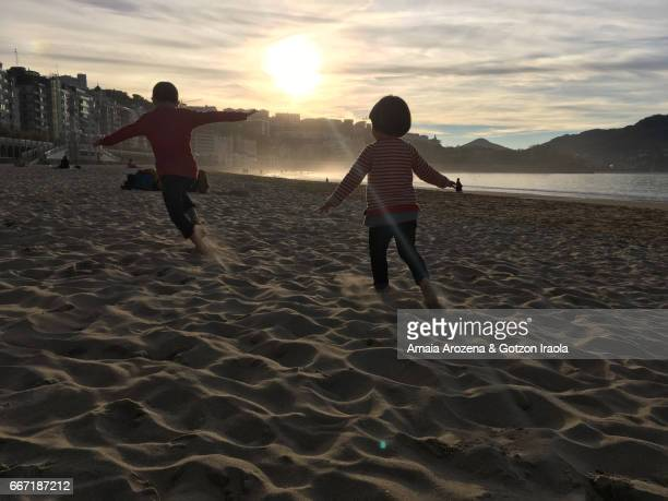 Two young brothers playing in La Concha beach at sunset. Donostia-San Sebastian, Basque Country