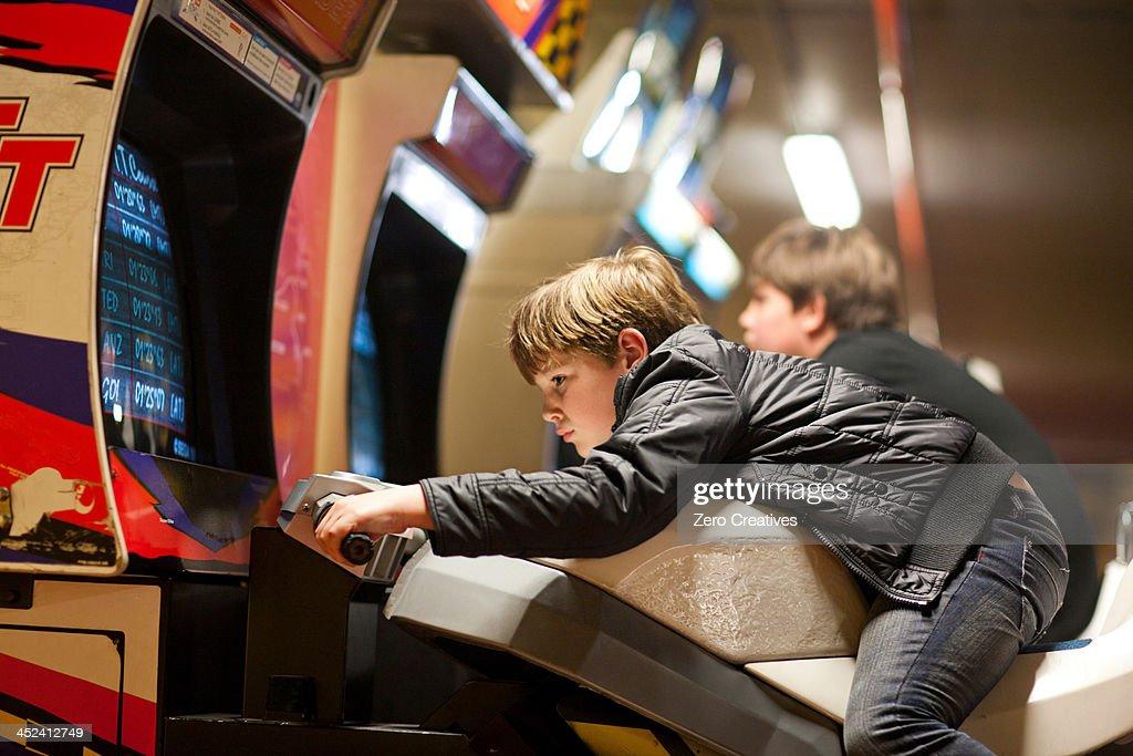 Two young brothers playing on driving video games : Stock Photo
