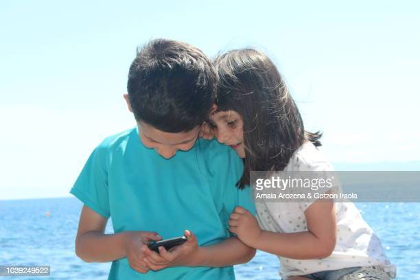 two young brothers playing with a smartphone - candid forum stock-fotos und bilder