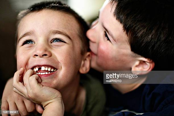 two young brothers smiling and cuddling - tooth fairy stock pictures, royalty-free photos & images