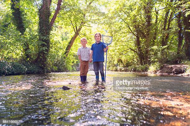 Two young brothers standing in a shallow river