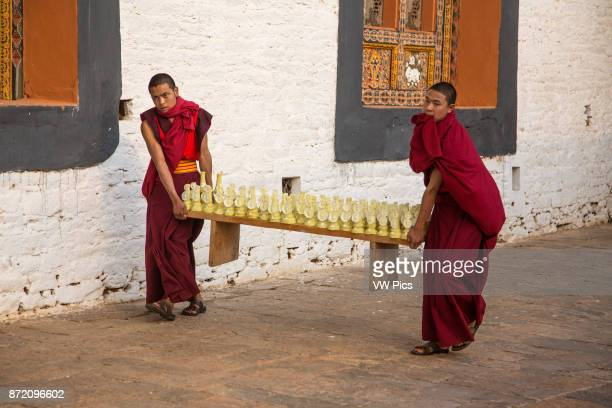 Two young Buddhist monks carrying torma or yak butter sculptures for a Bhuddist ceremony in the Punakha Dzong, Punakha, Bhutan.
