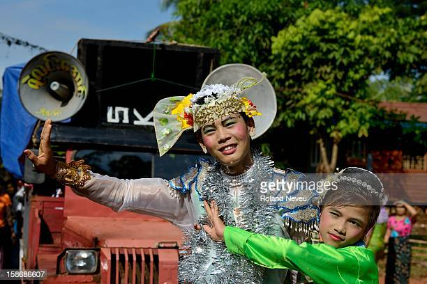 Two young Burmese men dressed as women are entertaining a group of citizen of a neighborhood of Moulmein who have organized a day of festivities to...