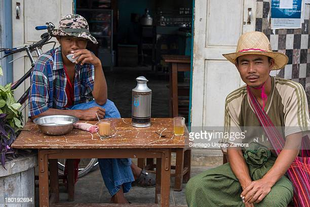 Two young Burmese men sitting relaxed having a tea outside of a tea shop in Nyaungshwe, Inle Lake, Shan State, Myanmar