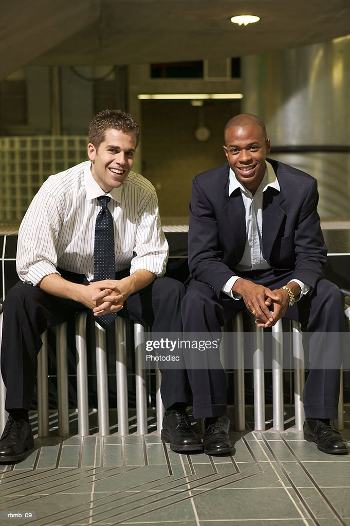 two young business men sit and smile on a bench in their office atrium : Foto de stock