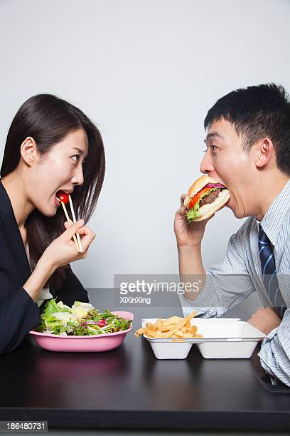 Two young business people eating a meal