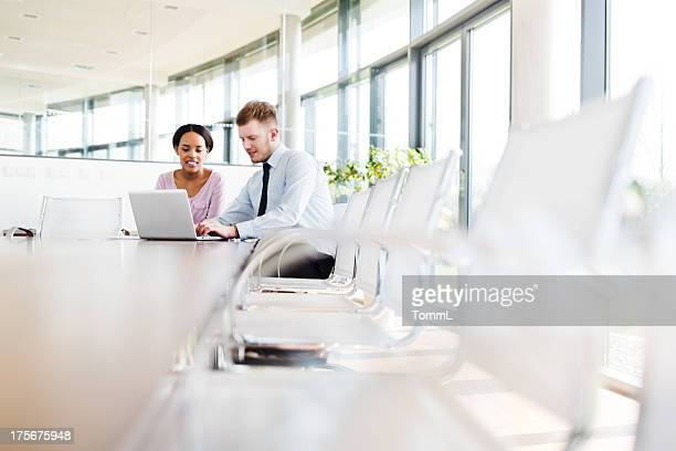 two young business people in modern office - brightly lit stock pictures, royalty-free photos & images