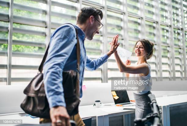 Two young business people in the modern office making high five.
