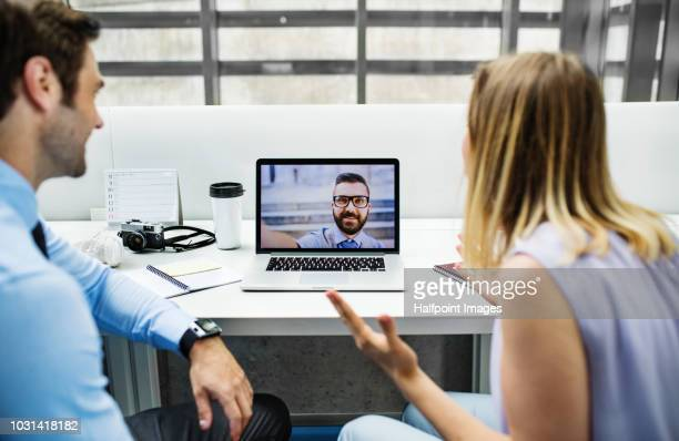 two young business people in the office making videocall. - finanzen und wirtschaft stock-fotos und bilder