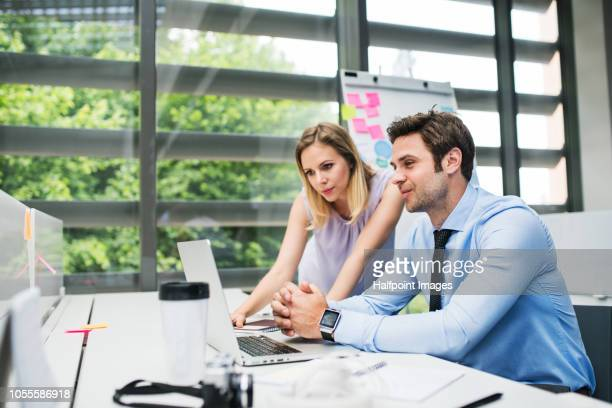 Two young business people in the office working together.