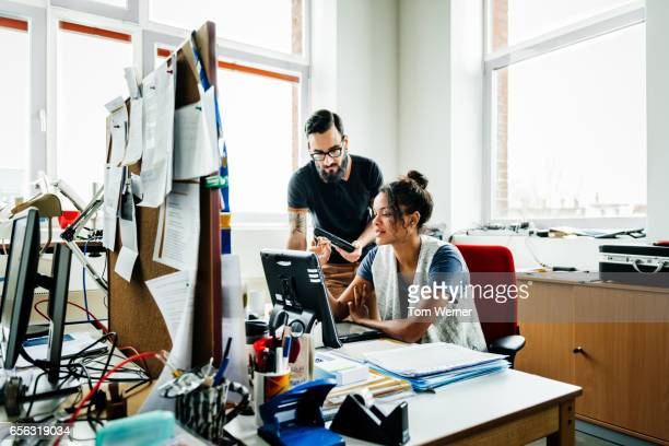 Two young business people meeting on a desk and discussing