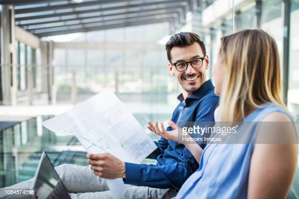 Two young business people talking together, using laptop and paper documents.