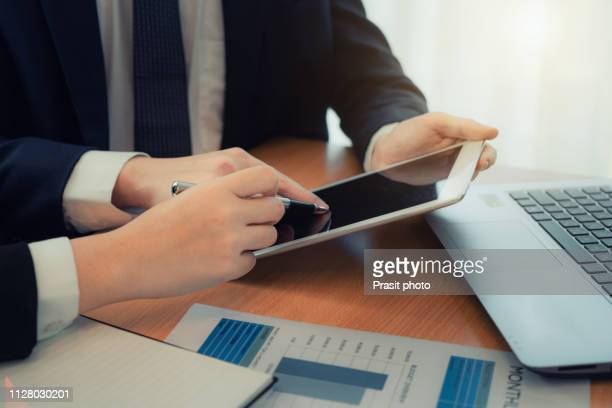 two young business people using touchpad at meeting in modern office. - obedience training stock pictures, royalty-free photos & images
