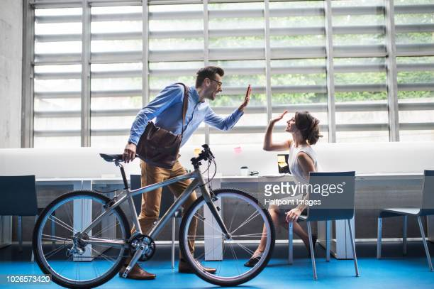 Two young business people with a bicycle in the modern office making high five.