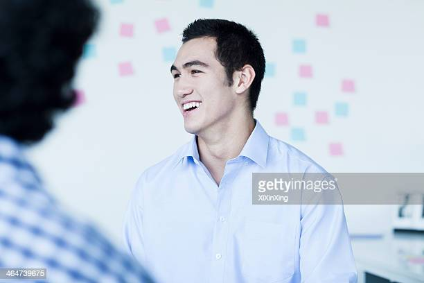 Two young businessman laughing and talking in the office