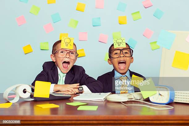 Two Young Businessmen at Desk Covered with Sticky Notes