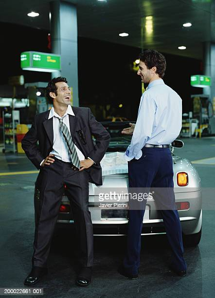 Two young businessmen beside sports car, referencing map, laughing