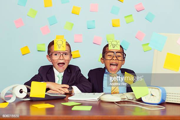 Two Young Businessmen Covered with Light Bulb Sticky Notes