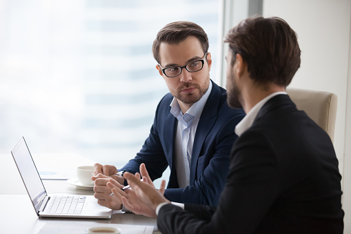 Two young businessmen discuss or plan project in office 1073415878