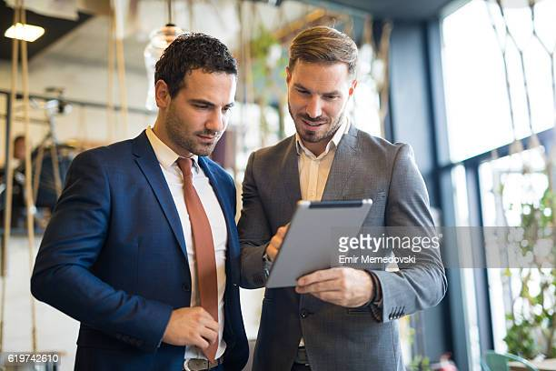 two young businessmen discussing business strategy using digital tablet - homme d'affaires photos et images de collection