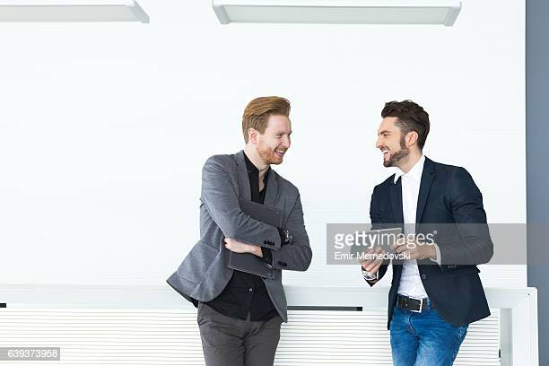Two young businessmen discussing documents and reports.