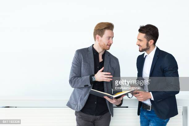 Zwei junge Geschäftsmänner über Dokumente und Berichte.