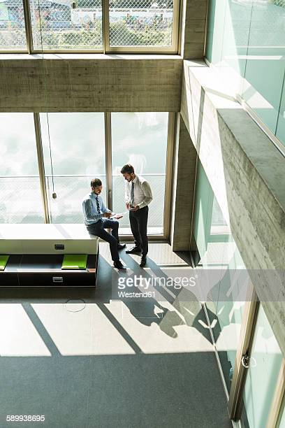 Two young businessmen discussing documents