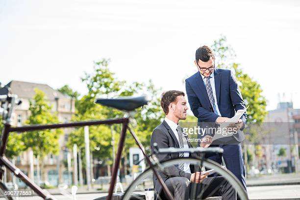 Two young businessmen discussing files outdoor