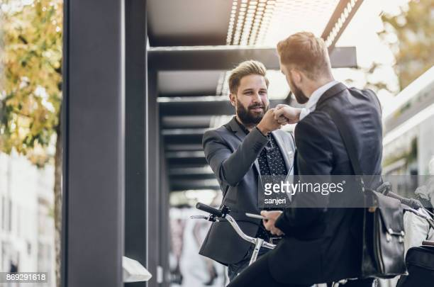 two young businessmen fist-bumping - fist bump stock pictures, royalty-free photos & images