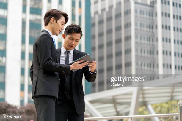 Two young businessmen having a meeting on the go