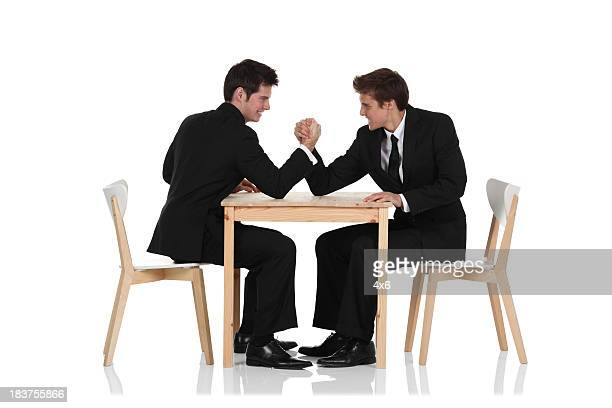 Two young businessmen having an arm wrestle