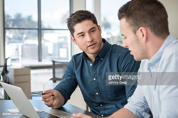 Two young businessmen in meeting using laptop