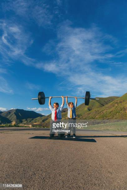 two young businessmen lifting weights together - resilience stock photos and pictures