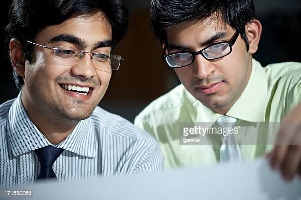 Two young businessmen looking at a sheet of paper.