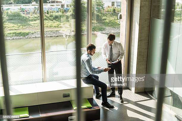 Two young businessmen looking at document and digital tablet