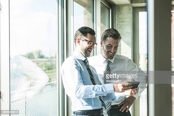 Two young businessmen looking at documents at the window