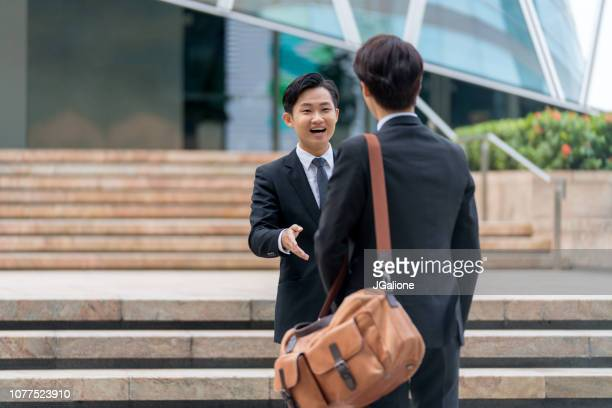Two young businessmen meeting outdoors