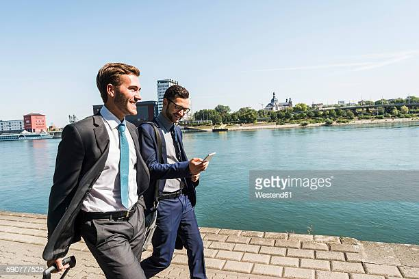two young businessmen on a business trip, walking by river - gemeinsam gehen stock-fotos und bilder
