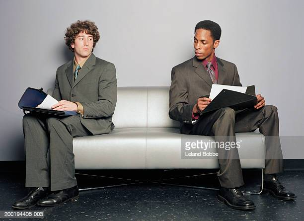 Two young businessmen on couch looking at each other's papers