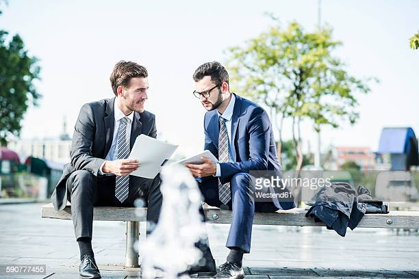 Two young businessmen sitting on bench, discussing files