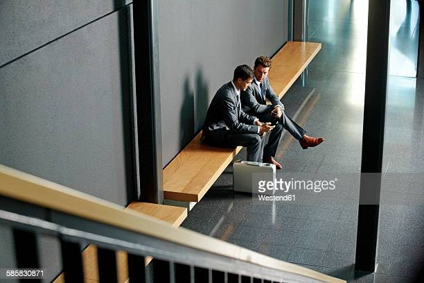 Two young businessmen sitting on bench using cell phone in office lobby
