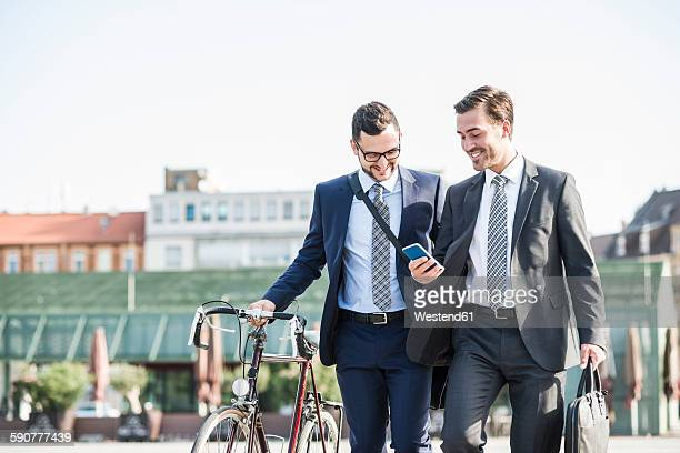 Two young businessmen walking in city, pushing bicycle