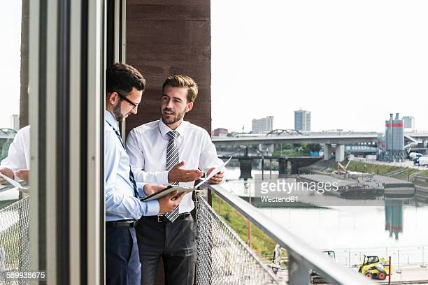 Two young businessmen with documents and digital tablet discussing on balcony