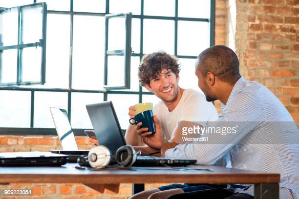 Two young businessmen working together in co-working space, using laptops